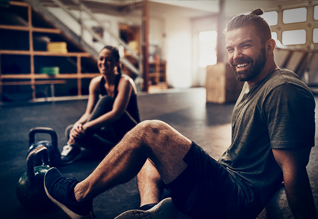 A young couple resting after completing a kettlebell work out