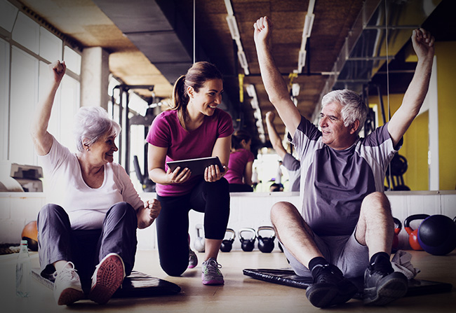 An elderly couple going through a series of stretches with their personal trainer
